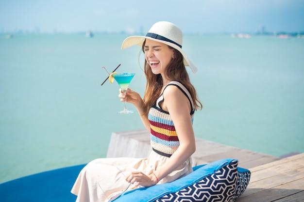 De mooie vrouw drinkt de drank van de ijszomer in het strand, de zomerconcept