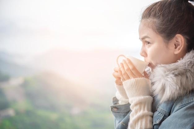 De mooie vrouw drinkt koffie in de ochtend met aardachtergrond