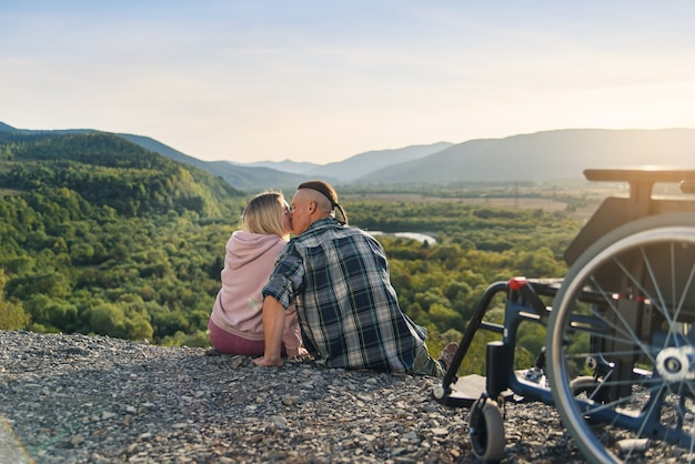 De mooie vrouw en haar wilsonbekwame echtgenoot zitten naast zijn rolstoel op de heuvel en kussen zachtjes.