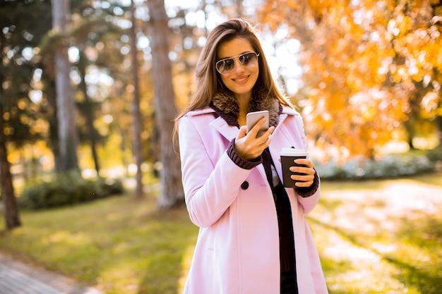 De mooie vrouw gebruikend telefoon en drinkt koffie in de herfstpark
