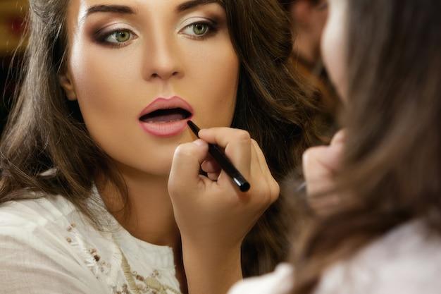 De mooie vrouw gebruikt potlood voor lippen