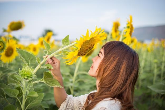 De mooie vrouw geniet van bloeiende zonnebloem op het zonnebloemengebied