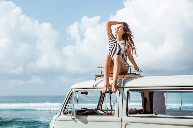 De mooie vrouw geniet van de aardzitting van de wegreis op het dak