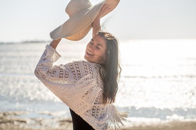De mooie vrouw glimlacht en houdt een hoed in haar handen. zee vakantie concept.