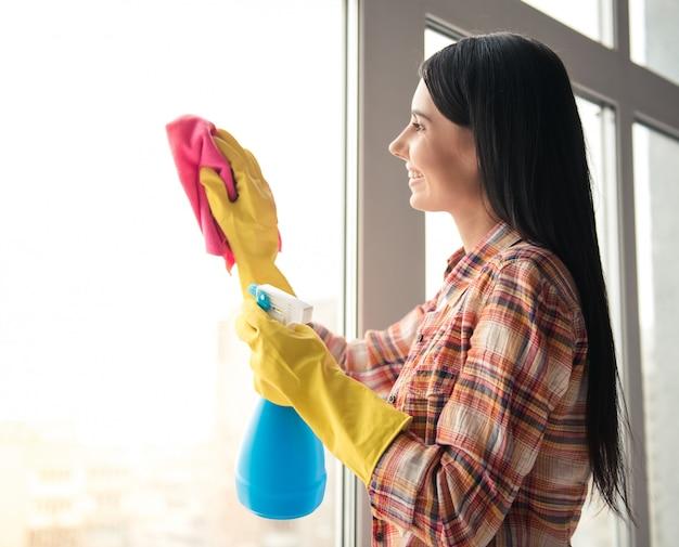 De mooie vrouw glimlacht terwijl thuis het schoonmaken van venster