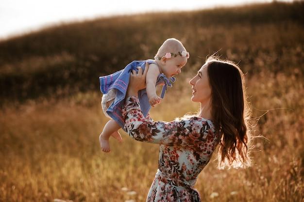De mooie vrouw heft haar aanbiddelijk babymeisje hoog op in de lucht en bekijkt haar glimlachend.