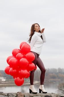 De mooie vrouw houdt ballons in haar handen