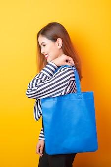 De mooie vrouw houdt blauwe stoffenzak