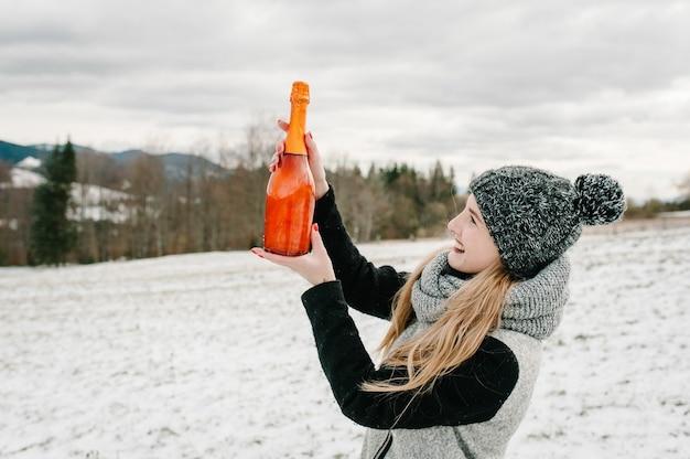 De mooie vrouw houdt een flessenchampagne tegen de achtergrond van de winterbergen. meisje in de besneeuwde winter, wandelen in de natuur. reis- en vakantieconcept. vakantie winterseizoen.