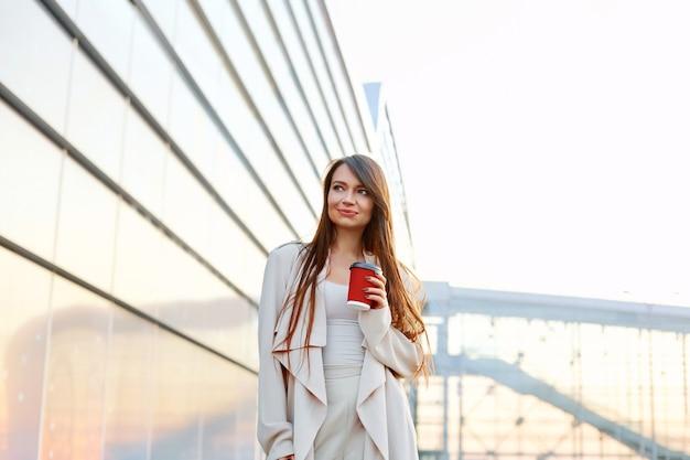 De mooie vrouw houdt koffie om te gaan