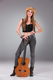 De mooie vrouw in een cowboyhoed en akoestische gitaar.