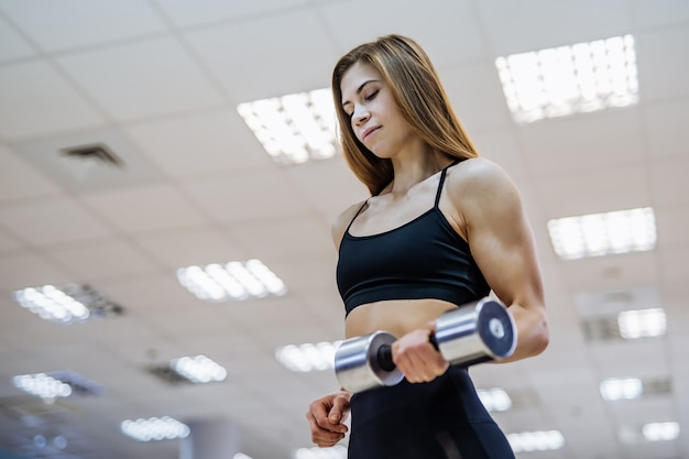 De mooie vrouw in een sportieve slijtageholding barbell in één dient de gymnastiek in.