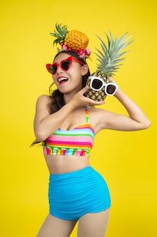 De mooie vrouw in een zwempak die een ananas houden stelt op geel