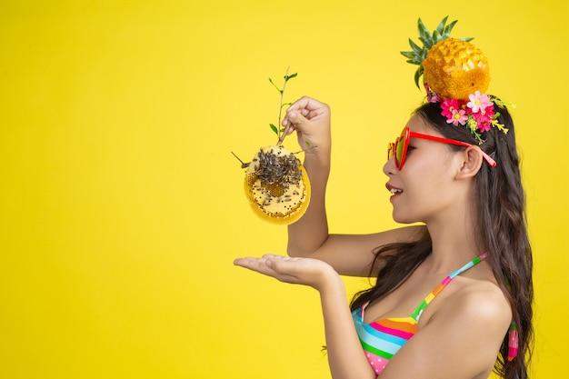 De mooie vrouw in een zwempak die een honingraat dragen stelt op geel