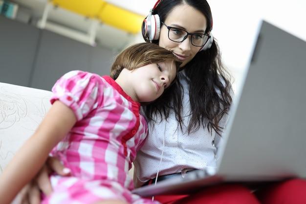 De mooie vrouw in glazen en hoofdtelefoons werkt voor laptop