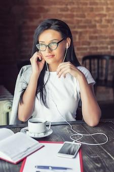 De mooie vrouw in glazen luistert muziek door haar smartphone bij koffie