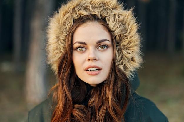 De mooie vrouw in jas met capuchon kijkt uit