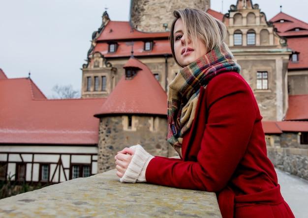 De mooie vrouw in rode laag blijft dichtbij kasteel