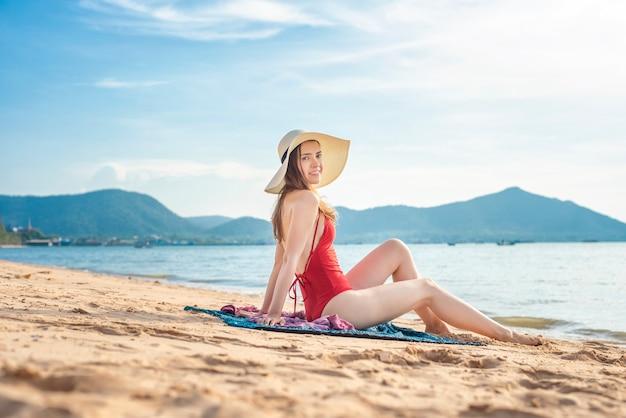 De mooie vrouw in rood zwempak zit op het strand