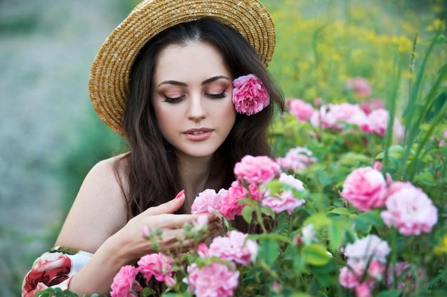 De mooie vrouw in strohoed verzamelt rozen in bulgarije in zonsopgang. serie.