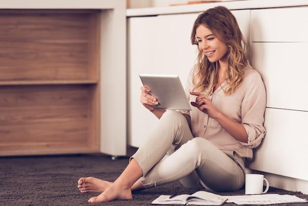 De mooie vrouw in vrijetijdskleding gebruikt een digitale tablet