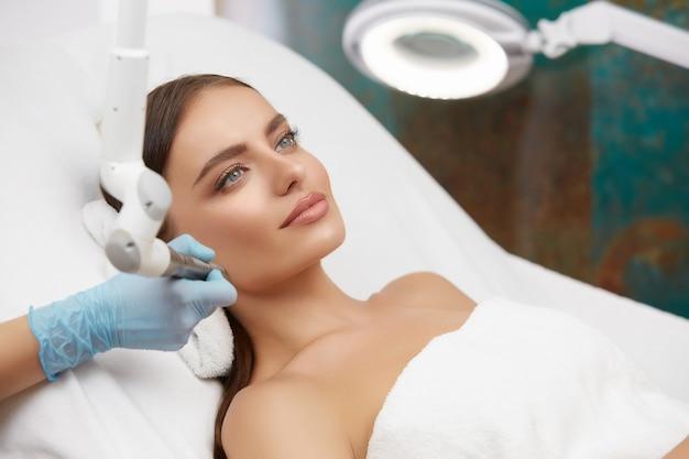De mooie vrouw is in de cosmetische salon, vooraanzicht