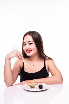 De mooie vrouw is klaar om de broodjes van smaaksushi te eten gebruikend houten die eetstokjes op wit worden geïsoleerd