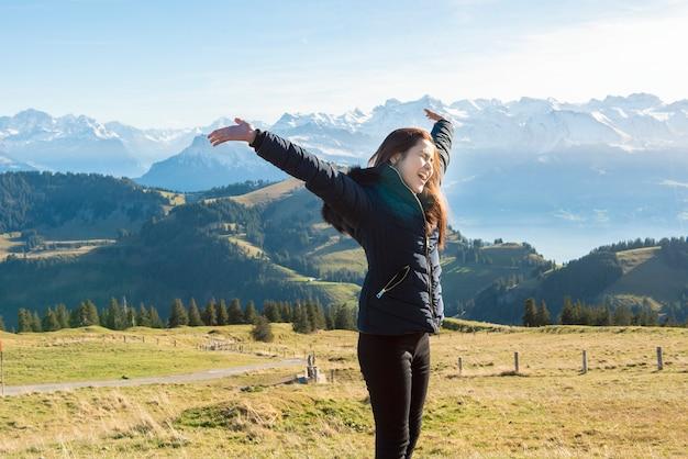 De mooie vrouw is vrijheid op de piekachtergrond van de sneeuwberg