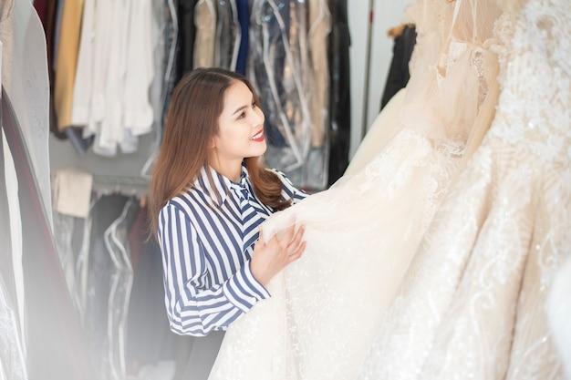 De mooie vrouw kijkt huwelijkskleding in huwelijkswinkel