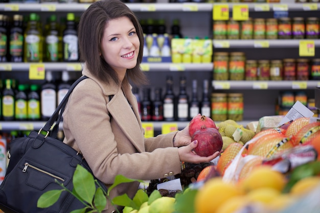 De mooie vrouw koopt bij supermarkt