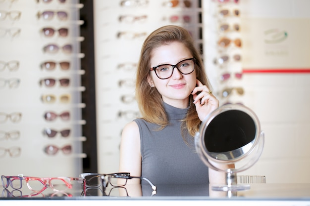 De mooie vrouw koopt nieuwe oogglazen