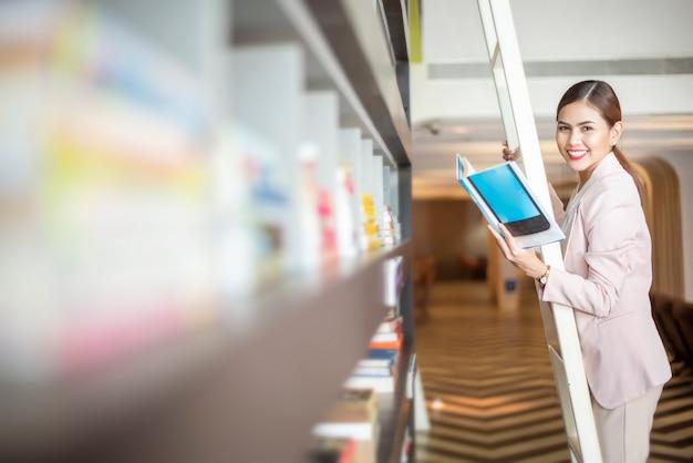 De mooie vrouw leest boeken in bibliotheek