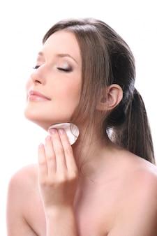 De mooie vrouw maakt gezicht met wattenstaafje schoon