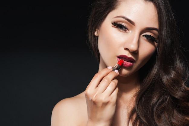 De mooie vrouw maakt make-up roze lippenstift op lippen toe te passen.