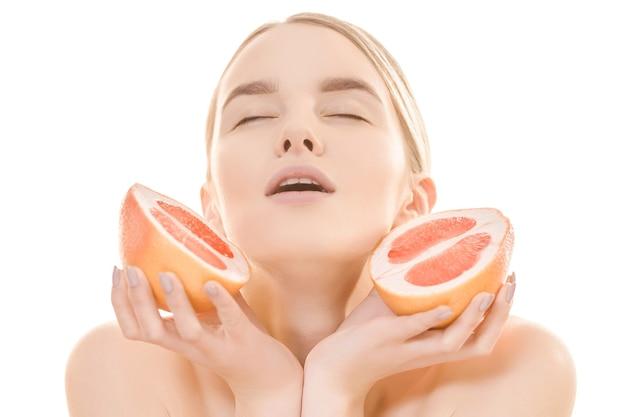De mooie vrouw met een grapefruit op de witte achtergrond