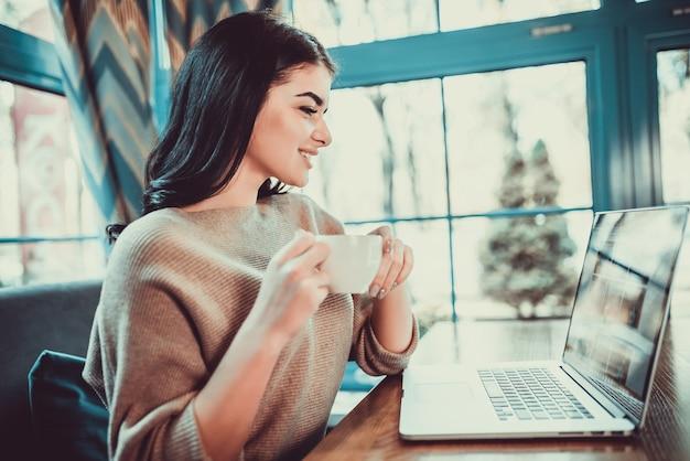 De mooie vrouw met een laptop drinkt een kopje koffie in het restaurant