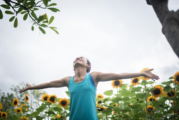 De mooie vrouw met het opheffen dient een gebied van zonnebloemen in de zomer in.