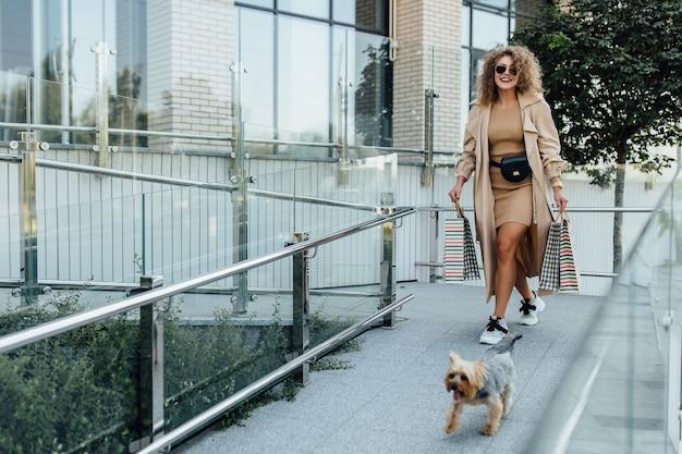 De mooie vrouw met krullend blond haar, met kleine hond en tassen op handen. winkelconcept.
