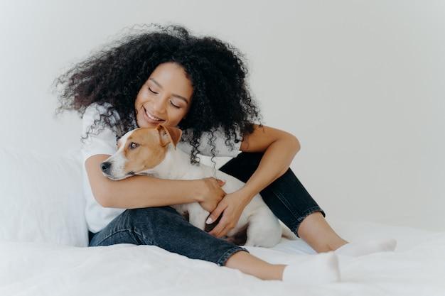 De mooie vrouw met krullend kapsel speelt en geniet van met schattige kleine hond in bed