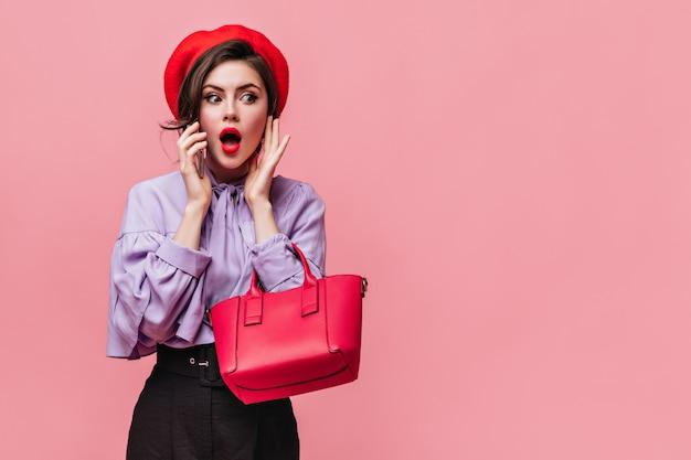 De mooie vrouw met rode lippenstift opende verrast haar mond. meisje in baret en stijlvolle blouse poseren met tas.