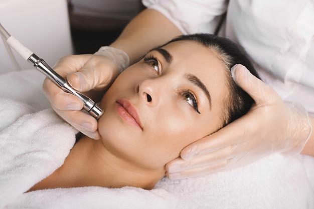 De mooie vrouw met zwart haar wacht om haar gezichtsprocedures bij de kuuroordsalon te beëindigen