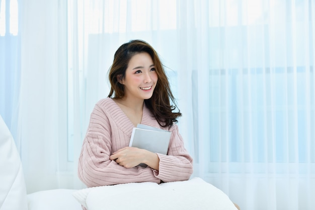 De mooie vrouw ontspant in een witte slaapkamer.