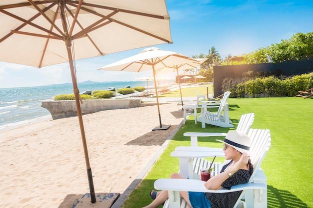 De mooie vrouw ontspant op het strand, onder paraplu