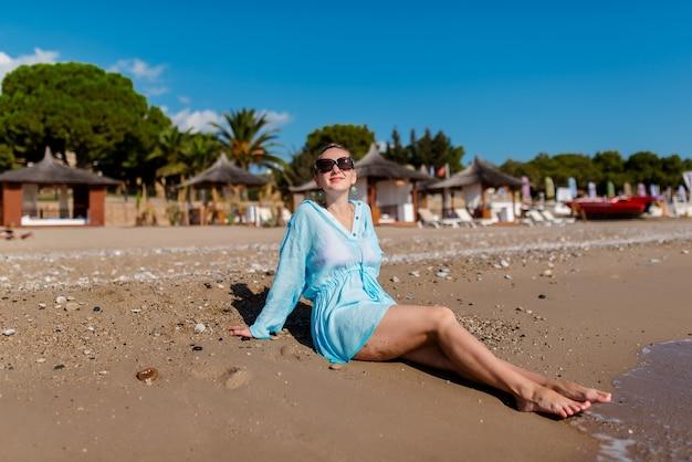 De mooie vrouw rust op het strand.
