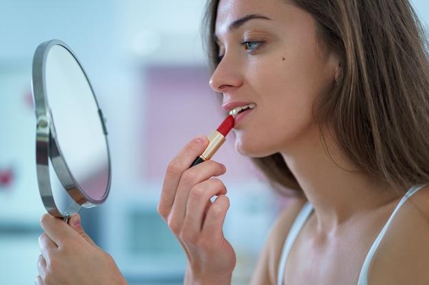 De mooie vrouw schildert lippen met rode lippenstift gebruikend een kleine ronde spiegel tijdens huismake-up in de ochtend