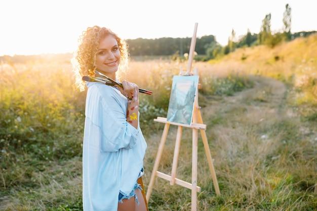 De mooie vrouw schildert. open lucht sessie. leuke vrouw tekent een foto bij zonsondergang. meisje kunstenaar
