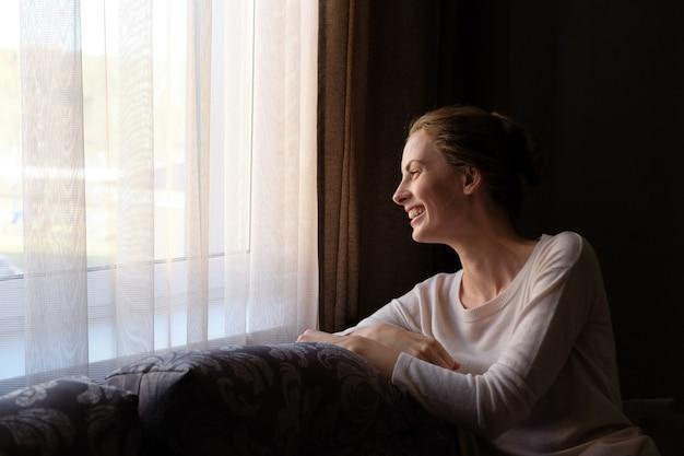 De mooie vrouw steekt thuis op de bank en het kijken aan het venster