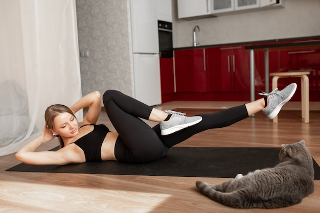 De mooie vrouw thuis in zwarte sportkleding leidt op een zwart tapijt naast een liggende kat op