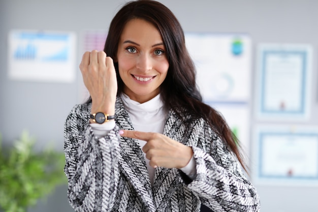 De mooie vrouw toont vinger op haar hand met klok.