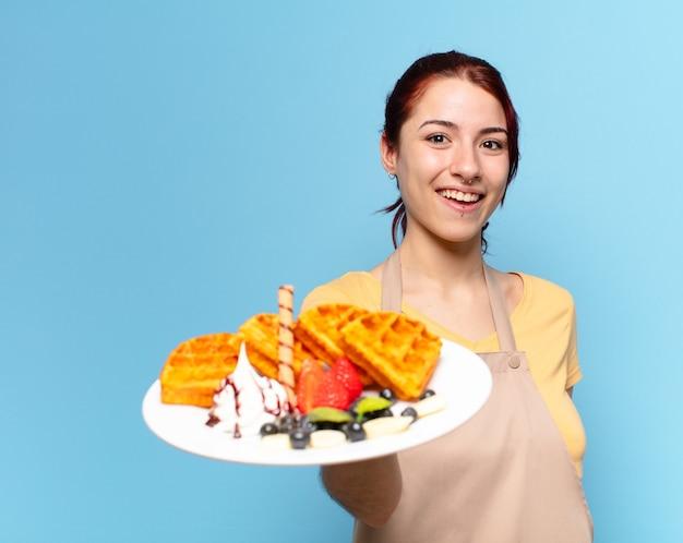 De mooie vrouw van de bakkerijmedewerker met wafels en cakes